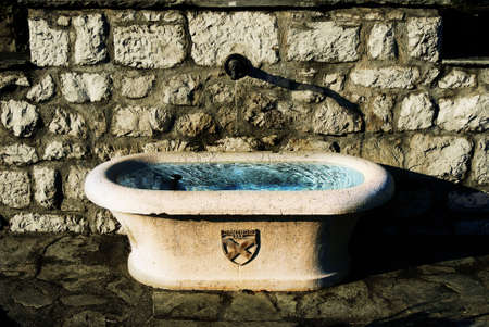 A water trough in Genthod-Bellevue, switzerland glimmers in the sun and brightly reflects the blue sky.