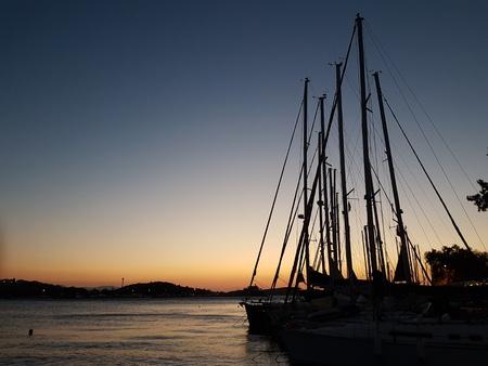 沈む夕日に帆極のシルエット 写真素材