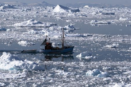 greenland: Fishing boat going through the icy waters of Ilulissat, Greenland Stock Photo