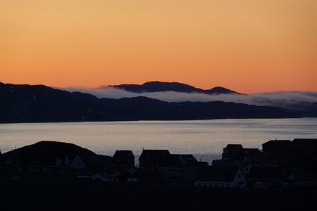 nuuk: Skyline after sunset in Nuuk, Greenland. The sky is tainted bright orange.