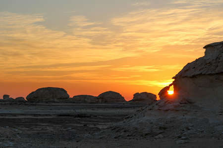 Sun rising in the Libyan desert, uncovering bizarre limestone formations, near Farafra in Egypt