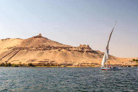 Sailboat on the Nile river at the shore of Aswan, tombs of the nobles in the background, Egypt Standard-Bild