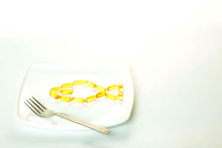 fish oil pills shaped like a fish on a platter with fork photo
