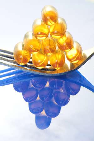 piramide nutricional: píldoras de aceite de pescado en un tenedor con una reflexión