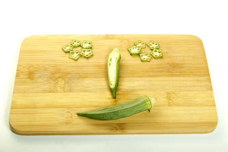 happy face Fresh raw okra isolated on white background  photo
