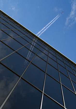 Office building with airplane and blue sky photo