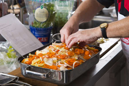a cook prepares a casserole with potatos and carrots photo
