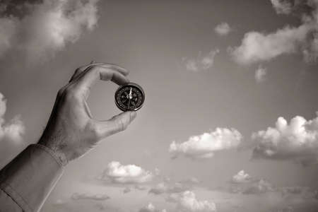 Man holding a compass over clear sky Stock Photo - 2583590