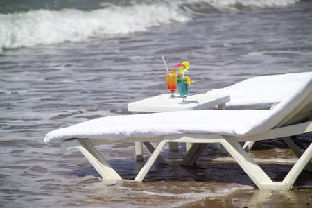 bleb: two cocktail glasses and longchairs on beach