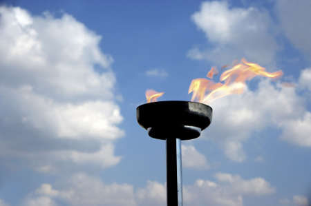 flambeau: burning torch  over blue sky Stock Photo