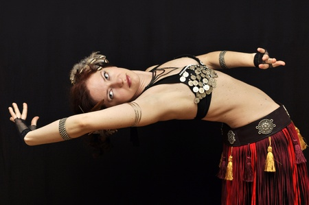 Dancer in fancy tribal skirt bending over backwards photo