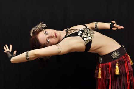bends: Dancer in fancy tribal skirt bending over backwards