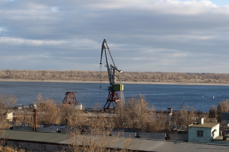 river bank: Landscape with a port crane at the river bank