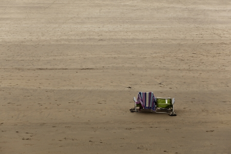 Two chairs left in an empty beach