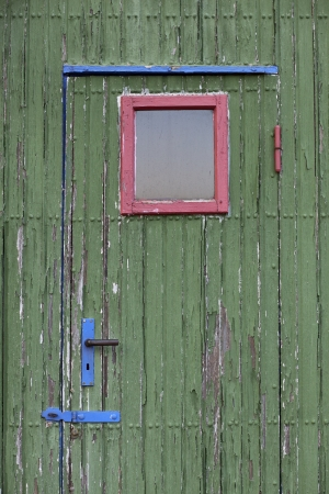 A red window on a green door with a blue handle Standard-Bild