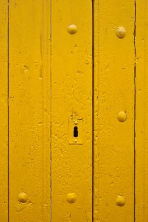 The keyhole of an old yellow door Standard-Bild