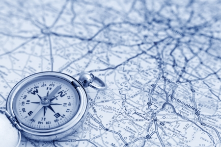 A compass on a road map pointing north