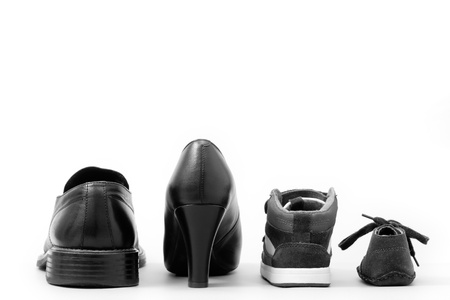 View of four isolated shoes (father, mother and two children). Concept of family