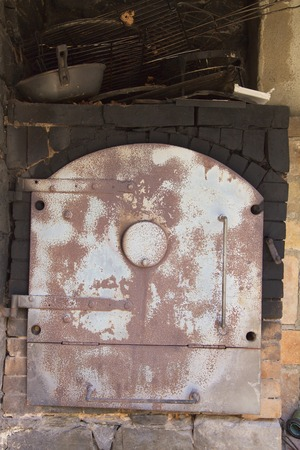 bakeoven: Old rusty cooking iron oven surrounded by dark bricks and pots on the top. Stock Photo