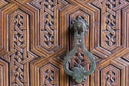 door knob: Iron Moroccan door knob on a traditionally carved wooden door (horizontal shot).