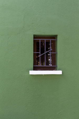 metal bars: A wooden window with metal bars on a green facade.