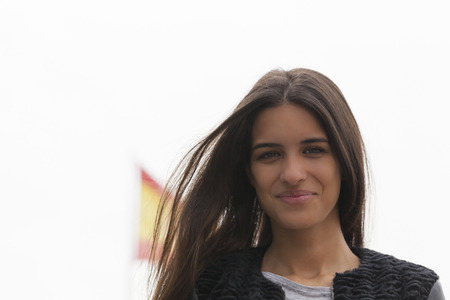 spanish flag: Young pretty woman with a Spanish flag blur in background.  The woman is looking and smiling at the camera.