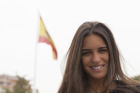 spanish flag: Young pretty woman with a Spanish flag blur in background.  Stock Photo