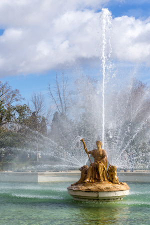 Medieval statue of golden queen sitting on throne in beautiful fountain Stock Photo