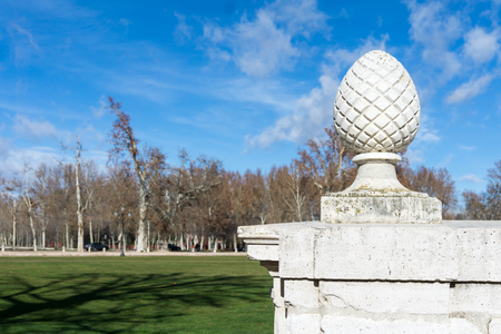 medieval garden with white stone egg statue against of blue sky