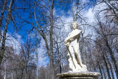 naked statue: Marble statue of naked man on top of medieval fountain against of leafless trees Stock Photo