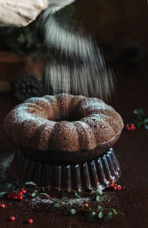 Holiday baking, The Best Chocolate Bundt Cake and a topping of powdered sugar in anticipation of the holiday! Pleasant and tasty treats for friends! Still life Stock Photo