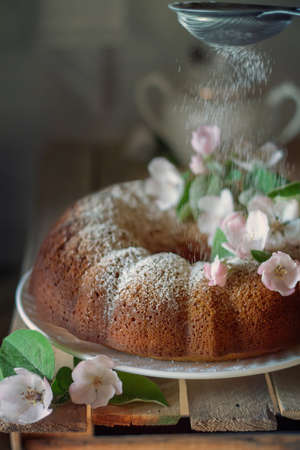 Round wreath cake with powdered sugar a pleasant treat to the tea table. The photo was taken using a lens of 50 mm.