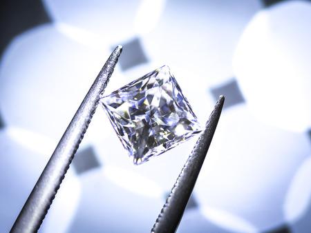 Princess Diamonds cut. in the tweezers on bokeh background. Stock Photo