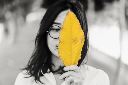 Blured photoTeen girl wearing glasses .standing holding yellow leaves black and white background