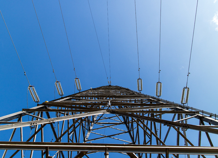 Looking up from the bottom of an electricity pylon, on the background of a bright blue sky.