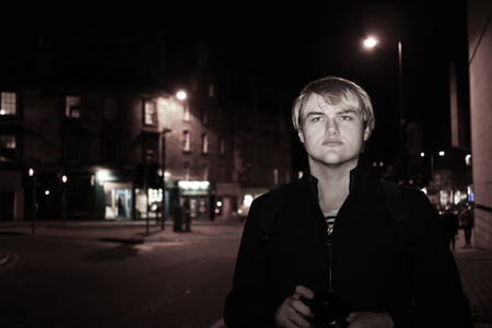 A handsome young man exploring the city of Edinburgh at night