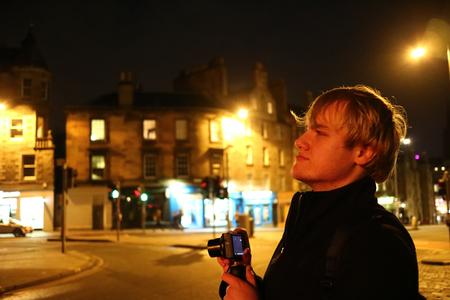 A young man preparing to take photos in Edinburgh at night