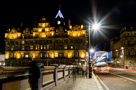 Edinburgh, United Kingdom - 12042017: Clock tower and moving bus in Edinburgh, with a tourist that looks over the bridge. Editorial