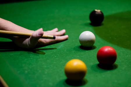 A hand preparing to play a pool shot, with a red and yellow ball, the black ball and the cue ball all visible. Stock Photo