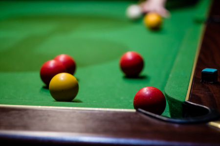 A hand preparing to play a pool shot into the corner