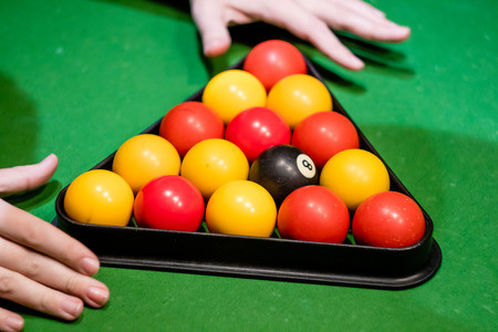 A pair of hands setting up a in pool with a c broken j. Banque d'images