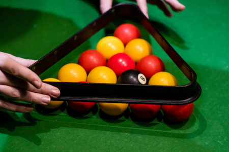 Hands taking away the triangle after setting up the balls in pool Banque d'images