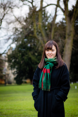 A beautiful young Japanese lady in the park wearing a coat and scarf, in portrait orientation