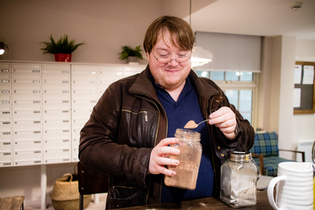 A man with a spoon of mystery brown powder, taken from a glass jar.
