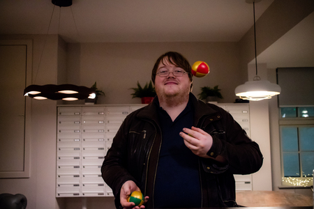 A man juggling in his house with three balls, taken from the front