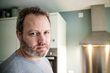 A man looking at the camera in the kitchen.