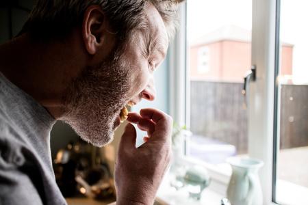A profile view of a man eating in the kitchen while looking out the window. Foto de archivo