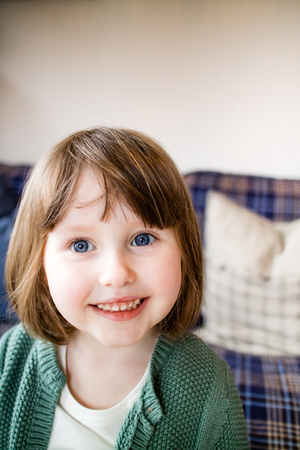 A cute child with blue eyes smiling sweetly into the camera