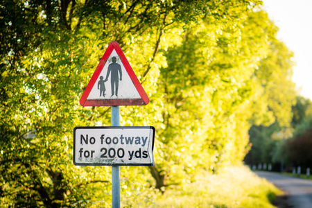 A sign warning drivers and pedestrians that there is no footway for 200 yards taken in the UK