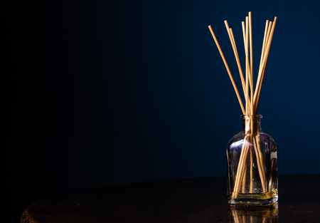 Reed diffusers in a small glass bottle on a table with a navy blue background with copy space on the left Stock fotó